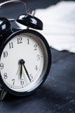 Wecker auf einer schwarzen Holzoberfläche Lizenzfreies Stockbild