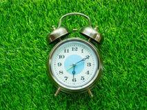 Wecker auf grünem Rasen Stockbild