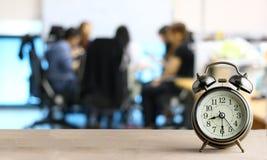 Wecker auf Holz mit unscharfem abstraktem Hintergrund der Geschäftsdiskussions-Leutegruppe oder des Sitzungsteams, Zeitkonzept an Lizenzfreie Stockfotos