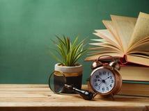 Wecker, Bücher und Anlage auf Holztisch Stockbild