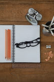 Wecker, Buch, Bleistift, Skala, Schauspiele und Bleistiftspitzer auf Holztisch Stockbild
