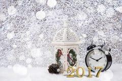 Wecker 2017 dekorativ auf weißer Tabelle mit Schneeflocke stockbilder