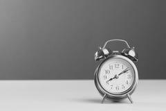 Wecker, der acht Uhr auf weißem Tabellenhintergrund zeigt Lizenzfreies Stockbild