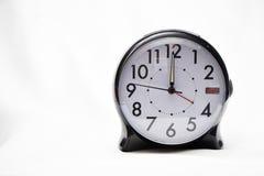 Wecker gegen den weißen Hintergrund, der 12 O-` Uhr zeigt Stockbild