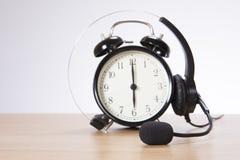 Wecker mit Kopfhörer auf Schreibtisch lizenzfreie stockfotografie