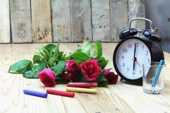 Wecker mit Rosen auf altem Holz stockfotos