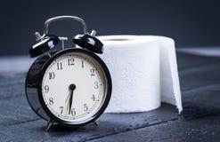 Wecker mit Toilettenpapier auf einer Tabelle Stockfoto