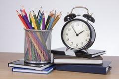 Wecker, Notizbücher mit farbigen Bleistiften Lizenzfreie Stockfotografie