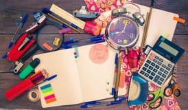 Wecker, Notizbuch, Stifte, Taschenrechner und Bleistifte Stockbild