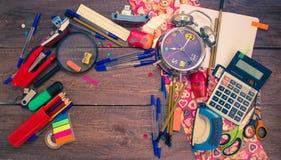 Wecker, Notizbuch, Stifte, Taschenrechner und Bleistifte Stockfoto
