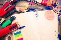 Wecker, Notizbuch, Stifte, Taschenrechner und Bleistifte Stockfotografie