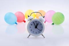 Wecker und bunte kleine Ballone Stockbilder