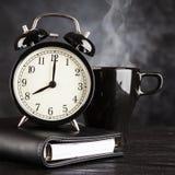 Wecker und ein Tasse Kaffee Stockfotos