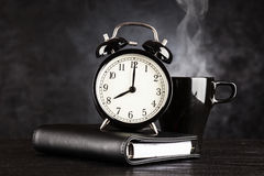 Wecker und ein Tasse Kaffee Stockfotografie
