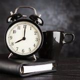 Wecker und ein Tasse Kaffee Stockbild