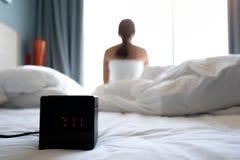 Wecker und Frau, die im Schlafzimmer aufwachen lizenzfreies stockfoto