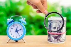 Wecker und Geld auf gr?nem bokeh Hintergrund Das Konzept von Zeit ist Geld Gesch?ftsfinanzideen einsparung finanziell lizenzfreies stockbild