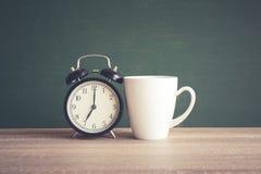 Wecker und Kaffeetasse auf Holztisch mit unscharfem backgrou stockfotos