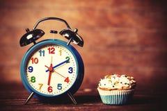 Wecker und kleiner Kuchen Lizenzfreies Stockfoto