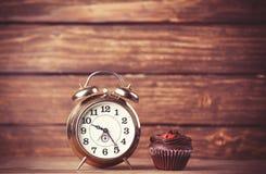 Wecker und kleiner Kuchen Lizenzfreie Stockfotografie