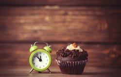 Wecker und kleiner Kuchen Stockbilder