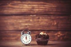 Wecker und kleiner Kuchen Stockfotografie