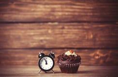 Wecker und kleiner Kuchen Stockfoto