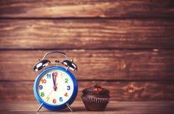 Wecker und kleiner Kuchen Stockfotos