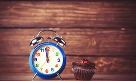 Wecker und kleiner Kuchen Lizenzfreie Stockbilder