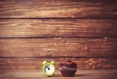 Wecker und kleiner Kuchen Lizenzfreies Stockbild