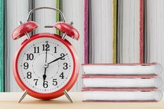Wecker und Notizbuch auf Tabelle mit Notizbuch ist ein Hintergrund Lizenzfreie Stockbilder