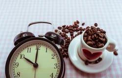 Wecker und reizende Kaffeetasse füllten mit Kaffeebohnen für t Lizenzfreie Stockbilder