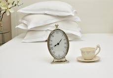 Wecker und Schale auf einem Bett Lizenzfreies Stockbild