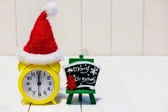 Wecker und Weihnachtsmann-Hut auf Holz Lizenzfreies Stockfoto
