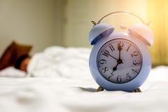 Weckersatz am 7:00 morgens mit Leuteschlafhintergrund Stockbilder