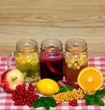 Weckgläser füllten mit heißem Ingwerzitrusfrucht-, Frucht- und Beerentee, Apfelwein, mit Beeren und Früchten im Vordergrund Stockfotografie
