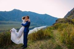 Οι νεολαίες wed πρόσφατα συνδέουν, το φίλημα νυφών και νεόνυμφων, αγκαλιάζοντας στην τέλεια άποψη των βουνών, μπλε ουρανός στοκ εικόνες
