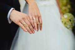Wed recentemente as mãos do par com alianças de casamento Imagens de Stock