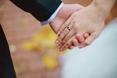 Wed recentemente as mãos do par com alianças de casamento Fotografia de Stock