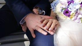 Wed recentemente as mãos do ` s dos pares com alianças de casamento Noivos com alianças de casamento em flores ou em ramalhete do Imagem de Stock Royalty Free
