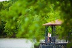 Wed recentemente os pares que abraçam ao lado de um lago foto de stock