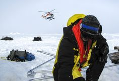 Helicopter assisted evacuation of a polar research camp. Weddell Sea, Antarctica – September 8, 2013: Scientist waiting for the landing of a helicopter royalty free stock photos
