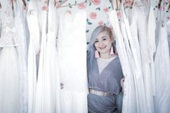 Weddign dress shop owner. Asian woman wedding dress shop owner take care for her products royalty free stock photo