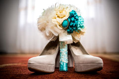 Weddind bridal accessories. Wedding bouquet and shoes on the carpet Royalty Free Stock Image