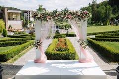 Weddind-Dekoration auf Freilicht Blumendekor eines schönen weißen Bogens Schöne beckground Ansicht von Bäumen Lizenzfreie Stockfotografie