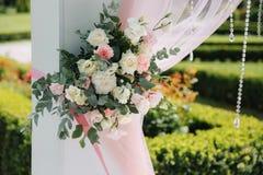 Weddind-Dekoration auf Freilicht Blumendekor eines schönen weißen Bogens Schöne beckground Ansicht von Bäumen Stockfoto