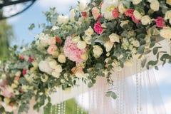 Weddind-Dekoration auf Freilicht Blumendekor eines schönen weißen Bogens Schöne beckground Ansicht von Bäumen Stockfotografie