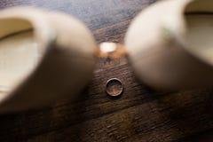 Wedding золотое кольцо в фокусе лежит на деревянной предпосылке другое обручальное кольцо между ботинками ` s невесты Стоковое фото RF