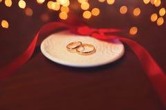 Wedding 2 золота кольца на таблице с красной лентой над торжеством освещают bokeh Стоковая Фотография RF