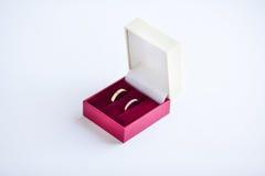Wedding золотые кольца в красной коробке на белизне Стоковые Изображения